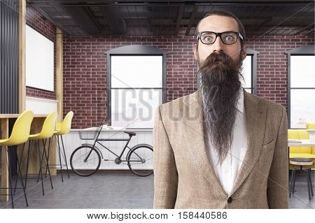 Baffled man standing in a cafe with yellow furniture large windows concrete floor and a bicycle near a brick wall. 3d rendering.