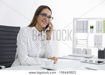 Bespectacled woman with brown hair is talking on the phone holding a pen and looking cheerful. Concept of communication