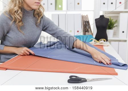 Close up of woman's hands folding a blue tissue on white table. Concept of sewing your own clothes