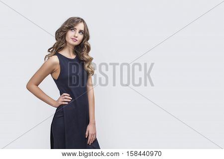 Portrait of thinking woman with her hand on the waist. She is standing in black dress and looking upwards. Mock up