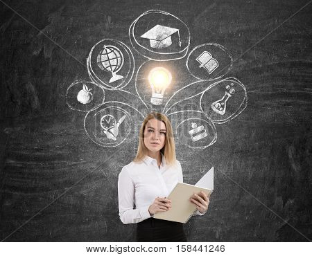Blond woman with a large notebook is standing near a blackboard with education sketches and a glowing light bulb