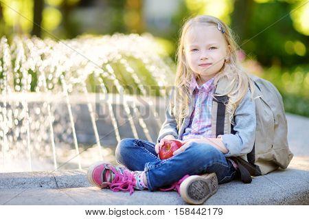 Adorable Little Schoolgirl In A City Park