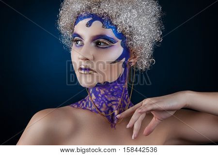 Portrait Of A Girl With Creative Make-up On A Dark Blue Background. Purple - Gold Makeup.