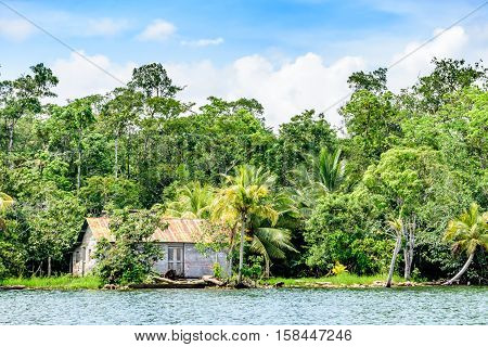 Wooden house with tin roof on riverbank in Guatemala, Central America