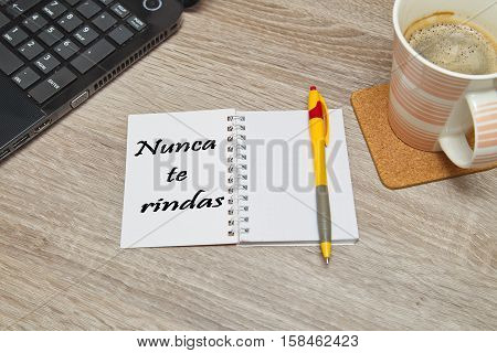 "Open notebook with Spanish text ""NUNCA TE RINDAS"" (Never Give Up) and a cup of coffee on wooden background. Top down view"