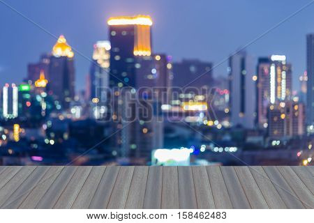 Opening wooden floor, Blurred lights cityscape, office building downtown at twilight