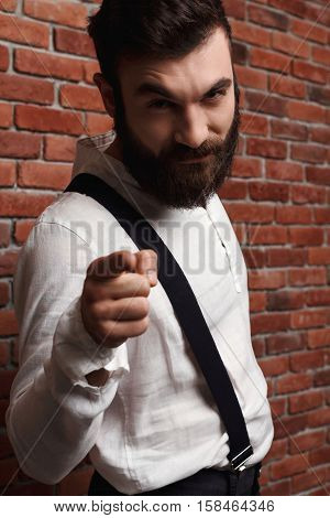 Young handsome man in suit with suspenders pointing finger at camera over brick background.