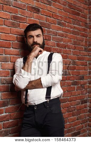 Young handsome man in suit with suspenders thinking posing over brick background. Copy space.