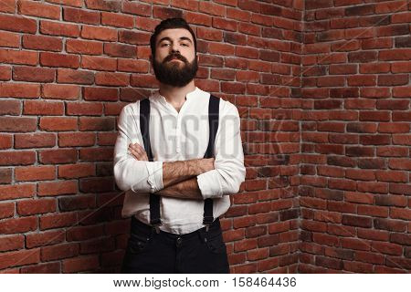 Young handsome man in suit with suspenders posing with crossed arms over brick background. Copy space.