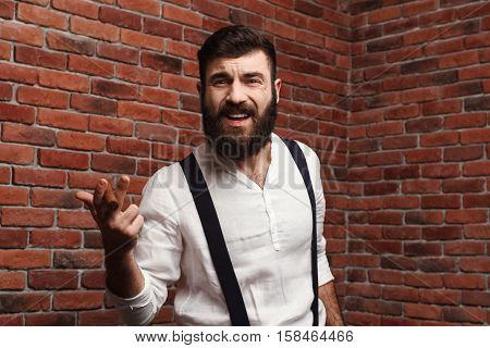 Brutal young handsome man in suit with suspenders smoking cigar over brick background. Copy space.