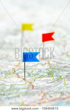 Three color flag pins on a map as travel destinations concept