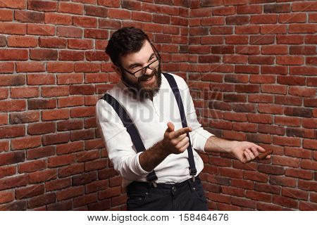 Young handsome man in suit with suspenders and glasses laughing over brick background. Copy space.