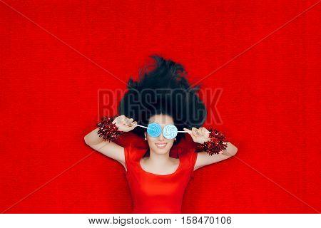 Smiling Christmas Girl Holding Lollipops on Red Background