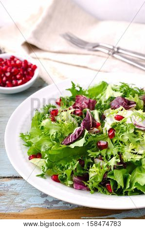Green salad with spinach, frisee, arugula, radicchio and pomegranate seeds on blue wooden background.