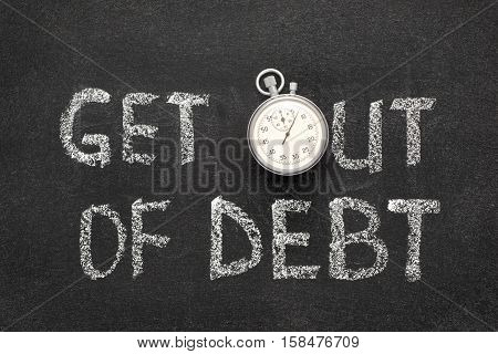 get out of debt phrase handwritten on chalkboard with vintage precise stopwatch used instead of O