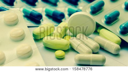 medical pills white, yellow and blue, small and one big round on the right of the photo, medicines in packing and scattered on a white table, yellow oblong heap lie, processed, preset,