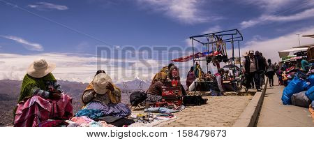 El Alto, Bolivia on October 1, 2015: Vendors at El Alto Market overlooking La Paz, one of the world's biggest markets. The women covering their faces are traditional Aymara people