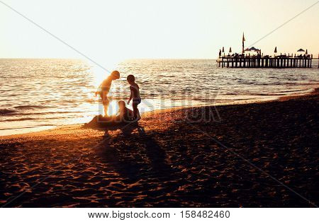 lifestyle people concept: three little boys silhouette on sunset beach playing in water, post card view