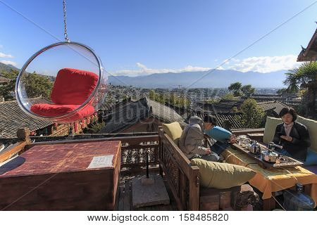 Lijiang, China - November 10, 2016: People Relaxing On A Couch And Enjoying The View Of Lijiang Old