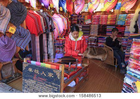Lijiang China - November 10 2016: Mosuo woman weaving inside her whorshop in Lijiang Old Town Yunnan