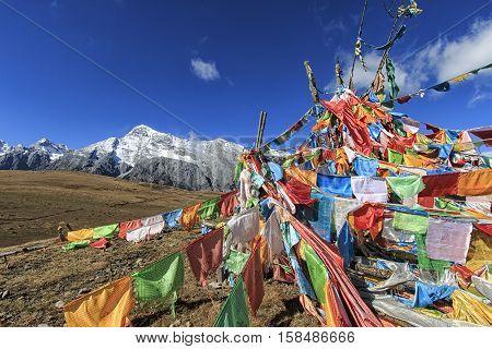 Lijiang China - November 11 2016: Tibetan Prayer Flags on foreground and Jade Dragon Snow Mountain on background