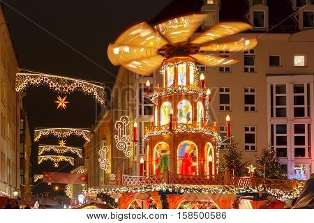 Decorated and illuminated Christmas street with carousel at night in Dresden, Saxony, Germany