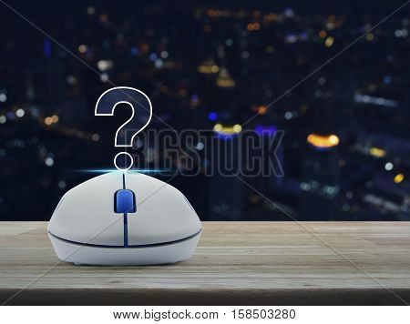 Wireless computer mouse with question mark sign icon on wooden table over blur light city tower Customer support concept