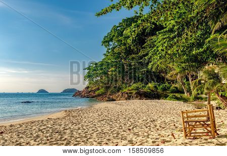 Empty bamboo chair on the sand of White Sand Beach, Koh Chang, Thailand. Nature vacation background. Beautiful tropical ocean or sea on sunny day