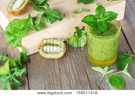 Ingredients for the preparation of: kiwi arugula mint and glass smoothies closeup