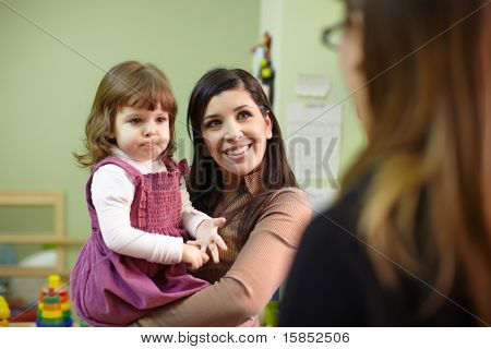 Educator And Mother With Little Girl At School