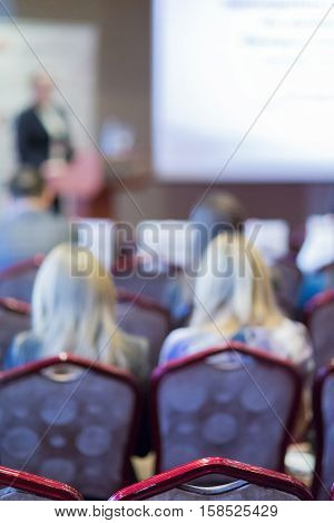 Female Speaker Speaking in Front of the Big White Screen During Conference.Vertical Shot