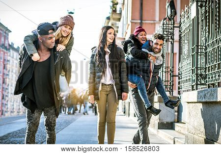 Group of multi-ethnic friends walking on the streets and smiling - Young people having fun outdoors