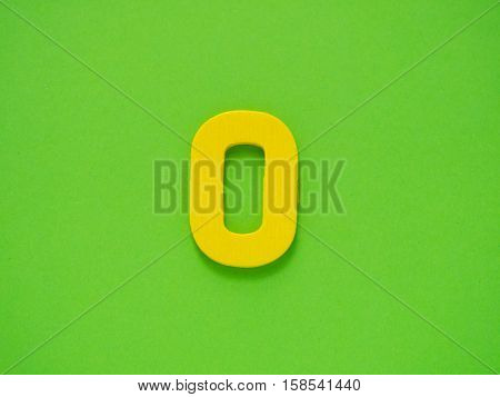 Capital letter O. Yellow letter O from wood on green background. Alphabet vowel.