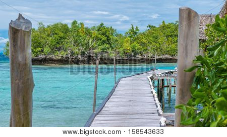 Pier of Bamboo Huts, Kordiris Homestay, Palmtree in Front, Gam Island, West Papuan, Raja Ampat. Indonesia