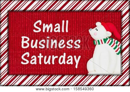Small Business Saturday message Red shiny fabric with a candy cane border and a Santa polar bear with text Small Business Saturday 3D Illustration
