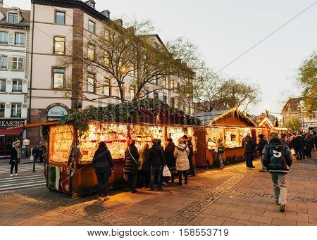 STRASBOURG FRANCE - DEC 8 2015: Traditional Christmas Market atmosphere and light decorations in Strasbourg France with tourists having fun and buying wooden toys souvenirs