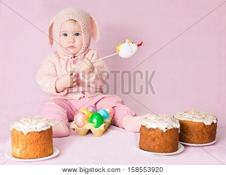 Easter bunny. Cute adorable baby girl in a costume of Easter rabbit with homemade easter cakes and a basket of eggs on pink background. Poster for Easter holiday.