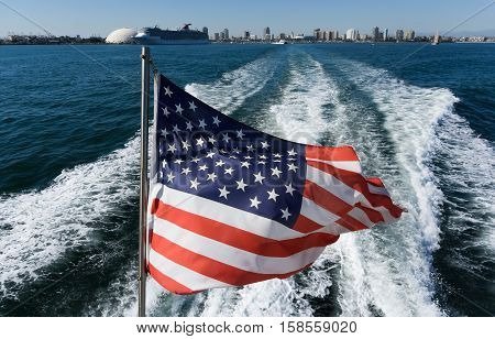 The American flag flies on the back of the boat. View from the boat on the American flag and the city.