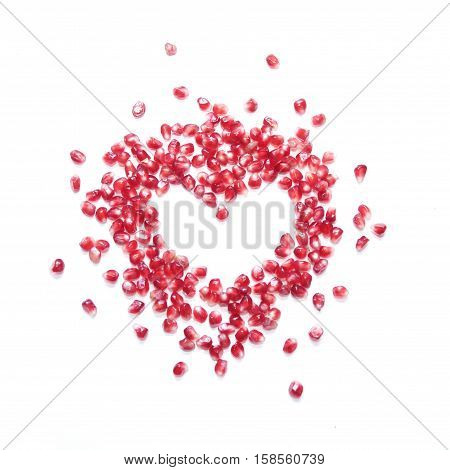 pomegranate seeds in shape of heart on white background