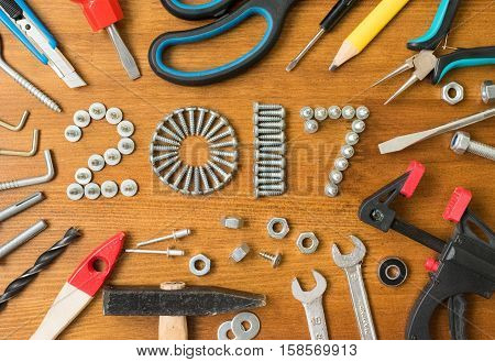 Happy new year 2017 composition with screws nails bolts dowels and tools on wooden background. New year. New year background. New year 2017. Concept constructions.