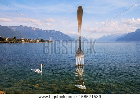 VEVEY, SWITZERLAND - September 02: modern art, 8-metre (26-foot) tall giant fork sticking out of a Geneva lake. Vevey, Switzerland on September 02, 2016