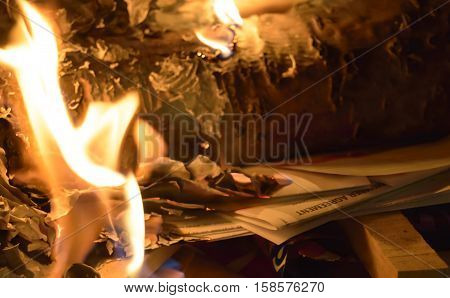 Getting out of debt holiday christmas debt image with copy space conceptual bills and spending habits buring credit card holder agreement in holiday fireplace with flames a pile of bills and statements of account with words cardholder agreement on fire