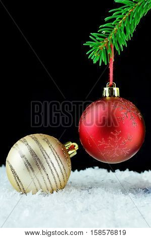 Red christmas ball on green bough. Beautiful christmas close-up decoration with black background. Gold christmas ball on white snow.