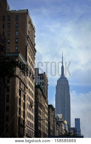 NEW YORK USA - MAY 17 2015: Empire State Building from the streets of New York City in the morning. Building illuminated by morning sun.