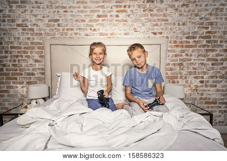 We never get bored. Smiling children having fun and playing game console while sitting on bed at home