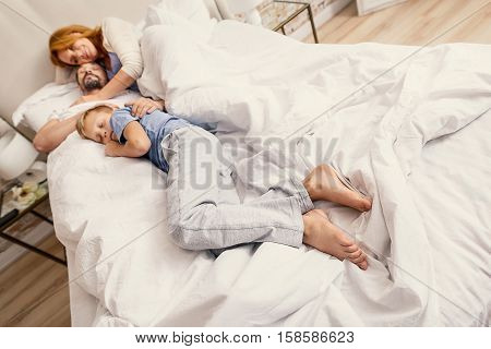 What a great loving moment. Little boy and his mother and father asleep in bed in early morning, embracing