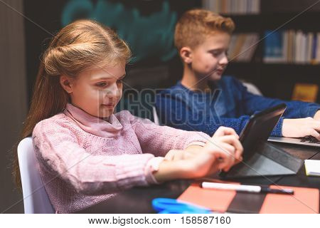 Attentive children searching information with their gadgets. Girl is using convenient black tablet.