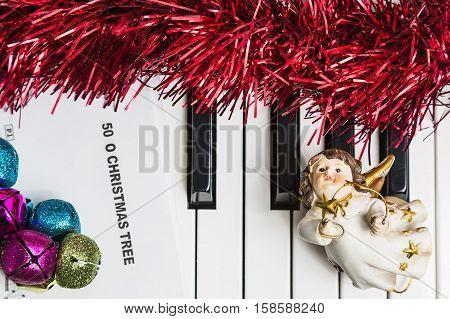 Christmas music concept. Printed music on the pianto with jingle bells angel and spangle.
