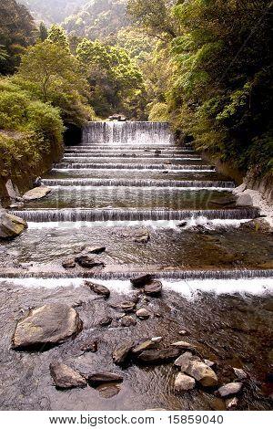 Cascada cae viejo río de ciruela con rocas