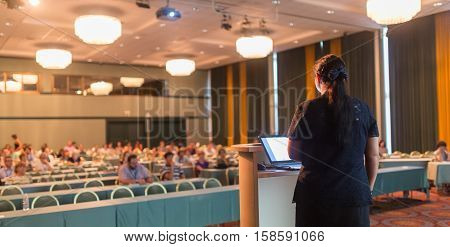Female speaker giving talk at business conference. Audience at the conference hall. Business and entrepreneurship. Successful businesswoman concept. Horizontal composition.